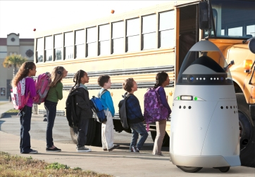 The K5 robot chaperones school children at a bus stop.